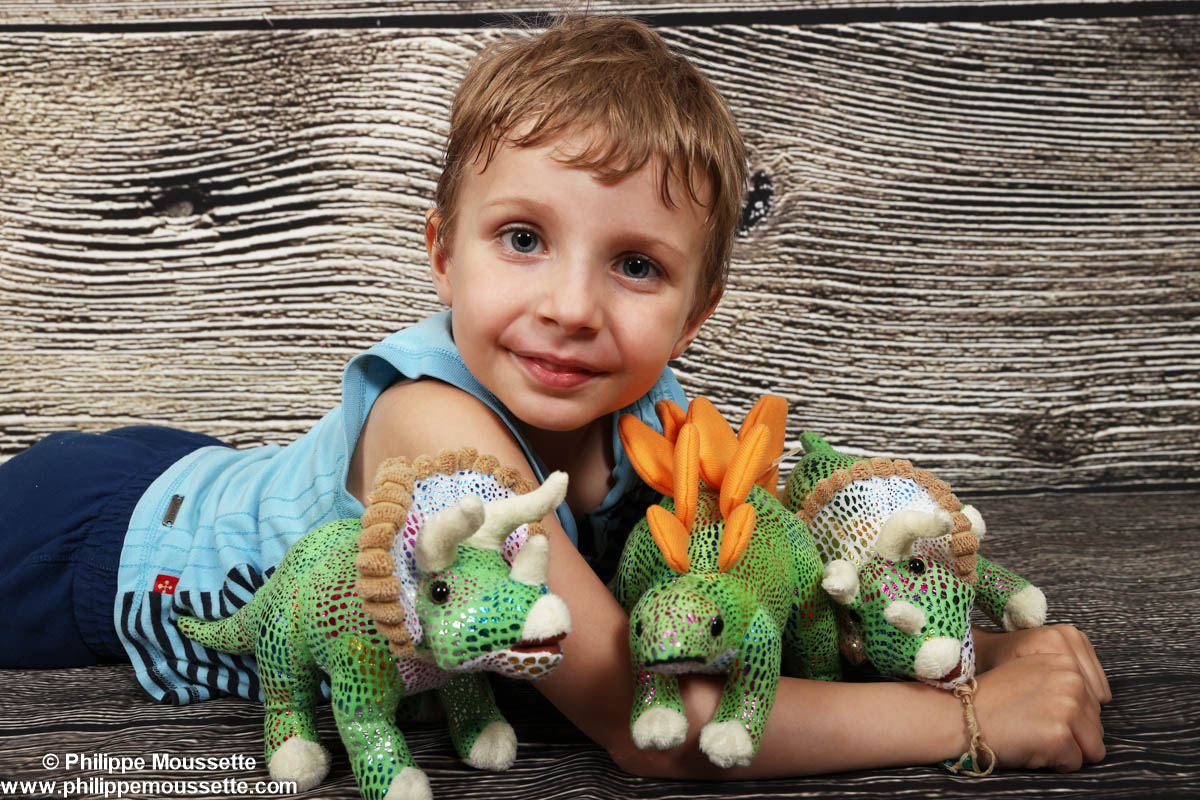 Garçon avec trois dinosaures en peluche